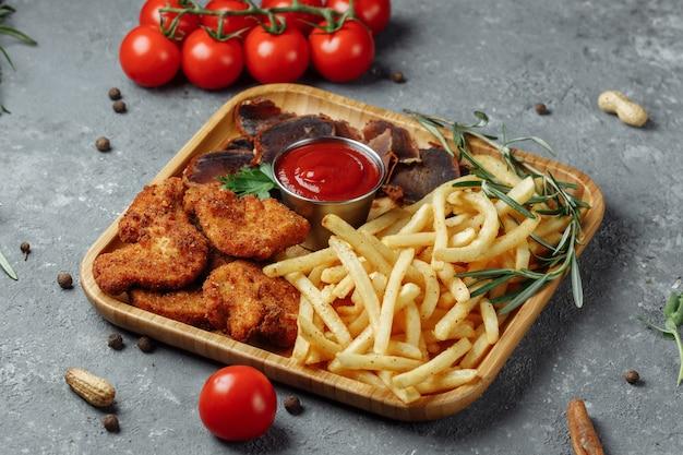 Piatto con snack. bocconcini di pollo impanati, patate fritte e jamon.