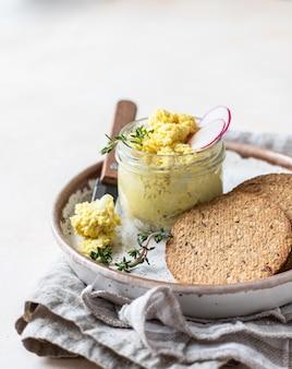 Piatto con tartellette, cracker multicereali con patè di uova o insalata servita con ravanelli e timo.