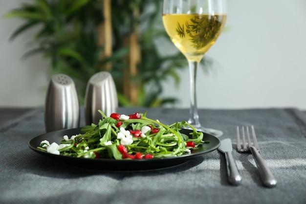 Piatto con gustosa insalata di rucola sul tavolo