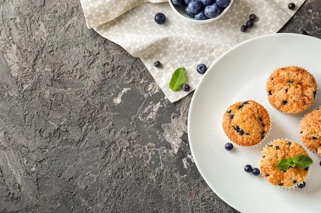 Piastra con gustosi muffin ai mirtilli sul tavolo
