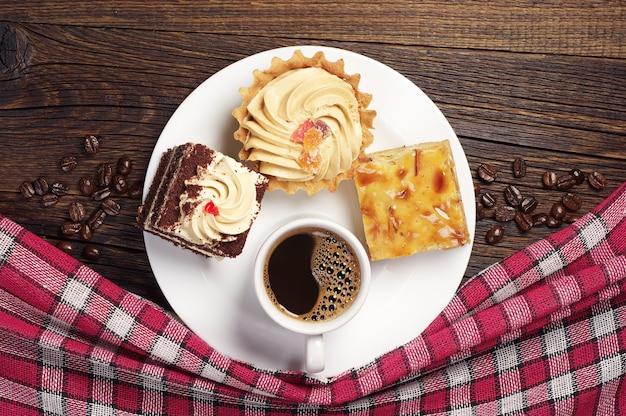 Piatto con gustose torte e tazza di caffè sul vecchio tavolo di legno. vista dall'alto