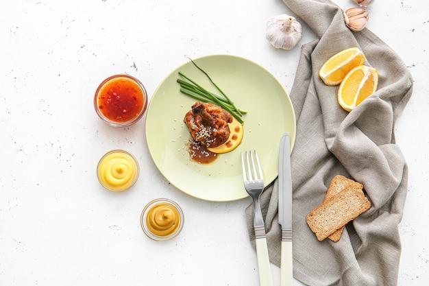Piastra con gustoso lecca-lecca di pollo su superficie chiara