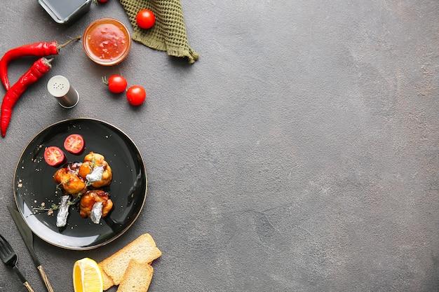 Piastra con gustosi lecca lecca di pollo su superficie scura