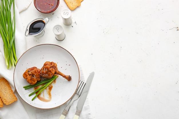 Piatto con gustosi lecca lecca di pollo su superficie chiara