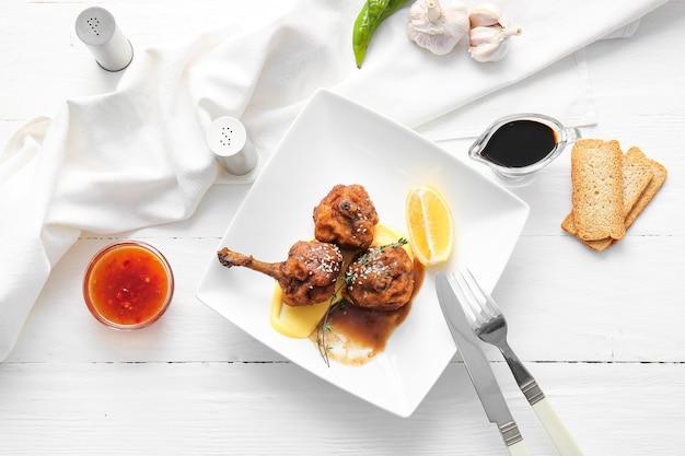 Piastra con gustosi lecca-lecca di pollo su superficie in legno chiaro