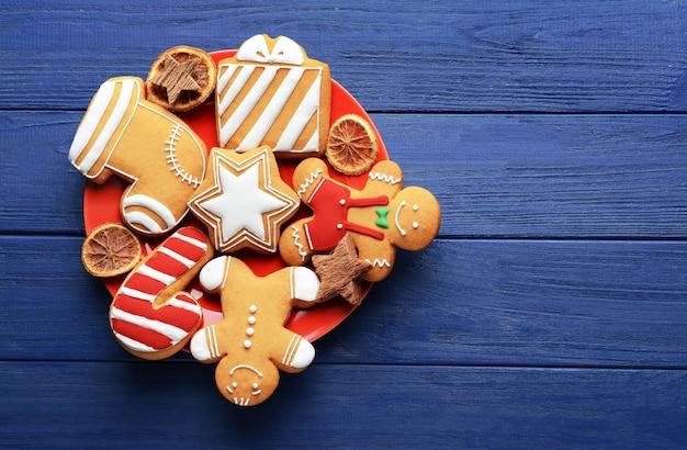 Piatto con gustosi biscotti di natale su tavola di legno
