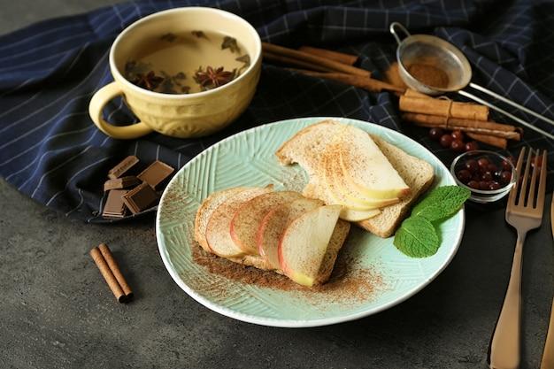 Piastra con gustosi toast alla cannella e fette di mela sul tavolo