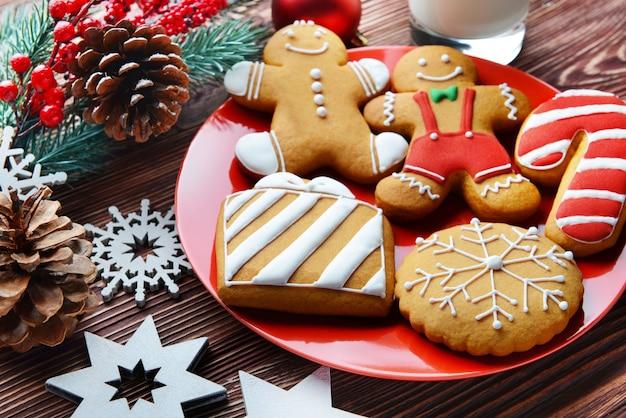 Piatto con biscotti gustosi e decorazioni natalizie su tavola di legno, vista ravvicinata