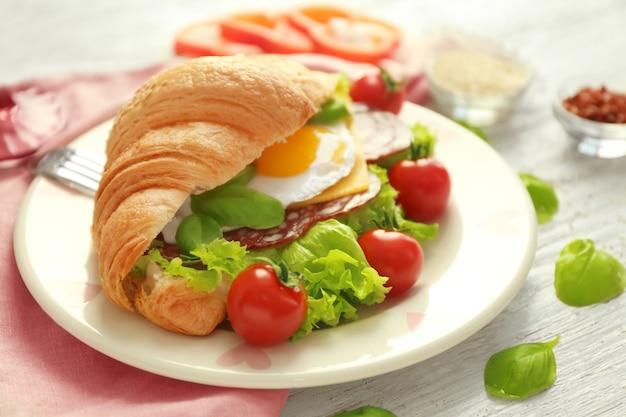 Piatto con gustoso panino croissant sul tavolo