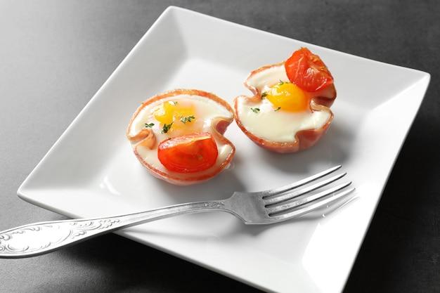 Piastra con gustose uova nel prosciutto sul tavolo