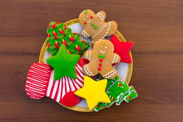 Piatto con gustosi biscotti natalizi festivi a forma di albero di natale, omino di pan di zenzero, stella e calzino di natale sul tavolo di legno. vista dall'alto