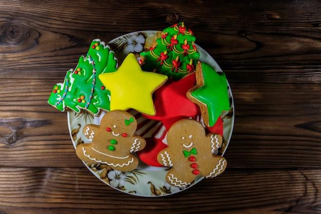 Piatto con gustosi biscotti di panpepato natalizio a forma di albero di natale, omino di pan di zenzero, stella e calza di natale sul tavolo di legno. vista dall'alto