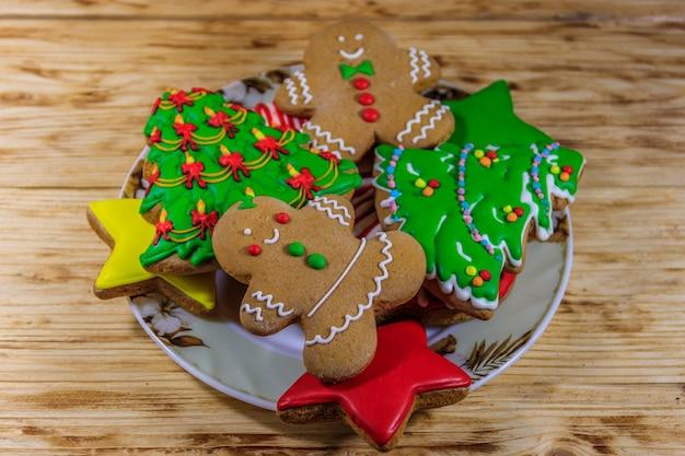 Piatto con gustosi biscotti di panpepato natalizio a forma di albero di natale, omino di pan di zenzero, stella e calza di natale sul tavolo di legno