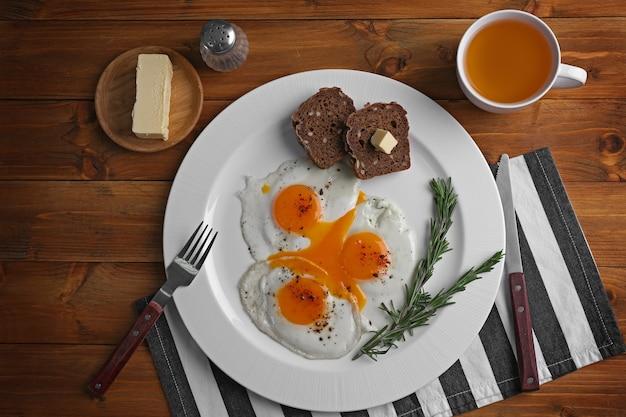 Piatto con gustose uova fritte e tazza di tè su fondo di legno