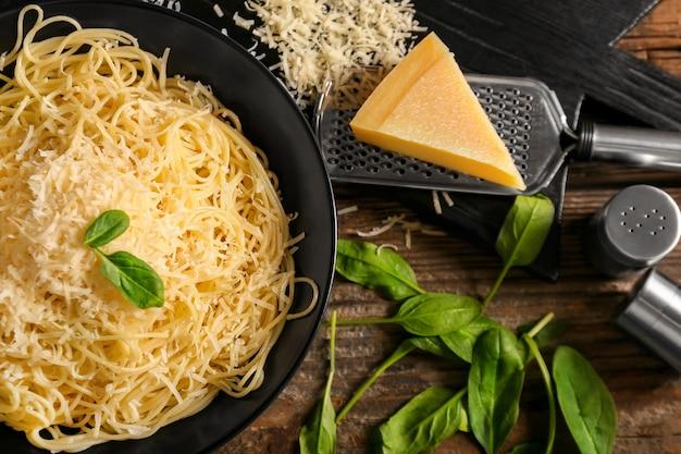 Piastra con gustosa pasta e formaggio sulla tavola di legno