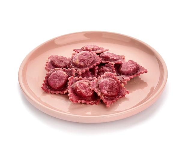 Piatto con gustosi ravioli su superficie bianca
