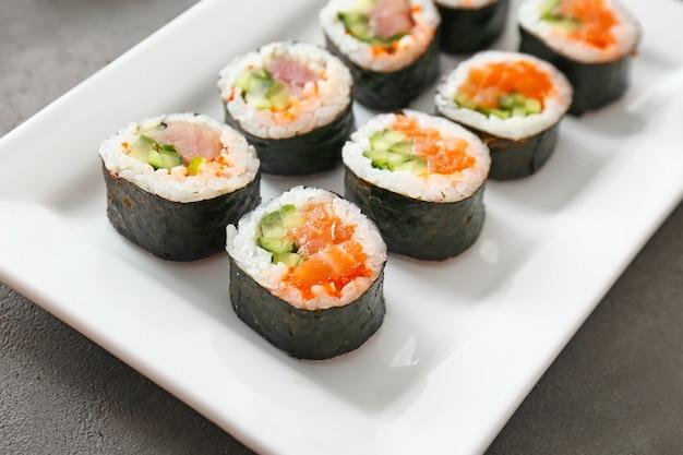 Piastra con gustosi rotoli di sushi sul tavolo