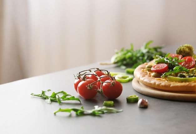 Piastra con gustosa pizza vegetariana sul tavolo