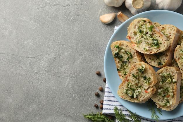 Piatto con pane all'aglio tostato e asciugamano su sfondo grigio, vista dall'alto