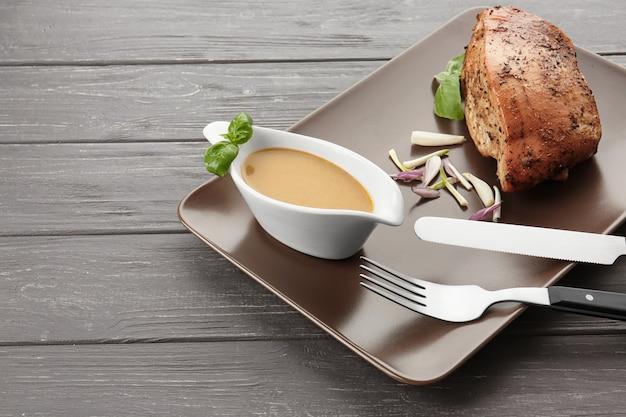 Piatto con sugo di tacchino in salsiera e carne al forno sul tavolo