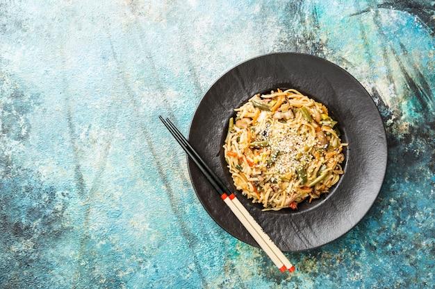 Piatto di wok o spaghetti saltati in padella con carne e verdure su pietra blu
