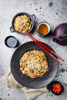 Piatto di wok o spaghetti saltati in padella con carne e verdure su pietra grigia