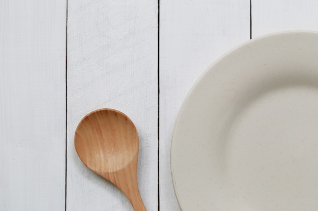 Piastra e cucchiaio di legno posizionati su sfondo di legno bianco e hanno lo spazio della copia per la progettazione nel vostro lavoro.