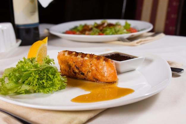 Pesce alla griglia placcato con contorni e salsa sul tavolo del ristorante