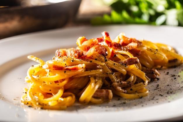 Spaghetti alla carbonara italiana placcati con prosciutto sopra.