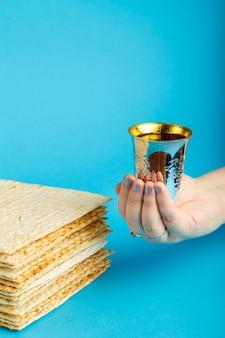 Piatti di matzo adagiati uno sopra l'altro su una superficie blu e un bicchiere di vino kiddush in mano