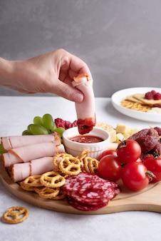 Piatti con antipasto, mano femminile che immerge una fetta di prosciutto in salsa su un tagliere rotondo con salsiccia, formaggio, cracker e frutta, primo piano.