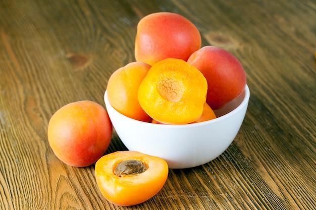 Piatti con albicocche fresche, alcune delle quali tagliate a metà, un bel colore di frutta