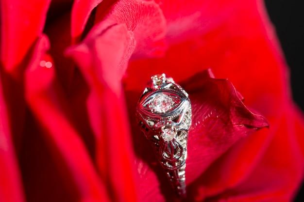 Anello in platino con un diamante su una rosa rossa, primo piano