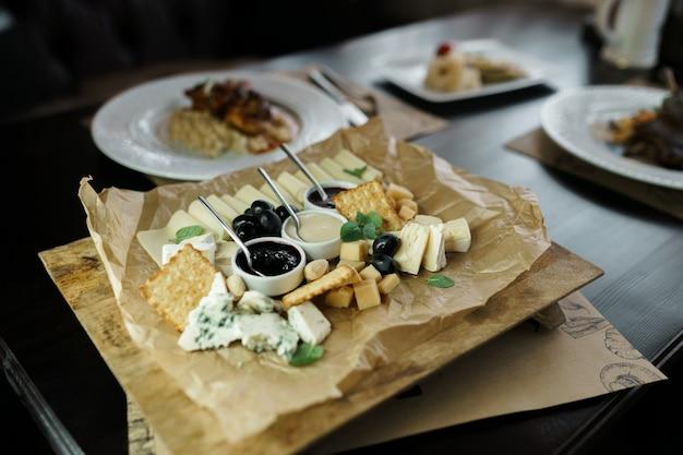 Piatto di: parmigiano, formaggio gouda, feta, formaggio erborinato con miele dolce e marmellata di mirtilli rossi, decorato con foglie di basilico profumate e olive. ottimo spuntino. piatto di formaggi