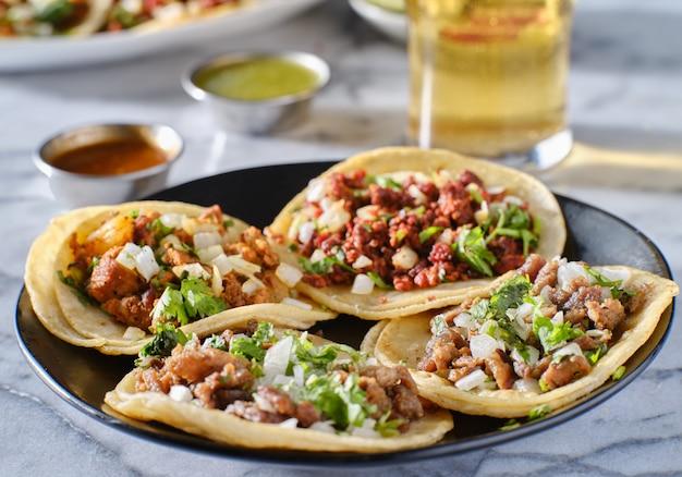 Piatto di tacos di strada messicani con carne asada, chorizo e al pastor in tortillas di mais