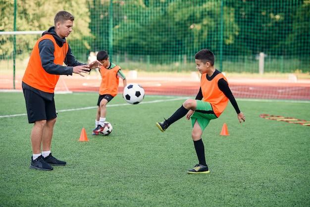 Giocatore in uniforme di calcio che risolve la palla calciare con l'allenatore sullo stadio