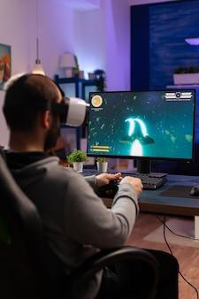 Uomo del giocatore che gioca al videogioco al computer potente a tarda notte indossando l'auricolare vr. giocatore entusiasta che utilizza il controller wireless per lo sparatutto spaziale di gioco del torneo virtuale a casa