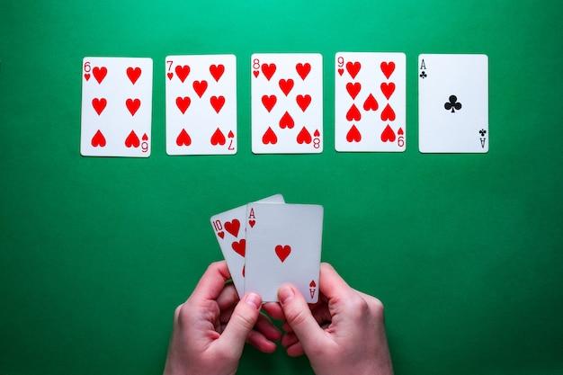 Giocatore al tavolo giocando e mostrando carte al gioco del poker. combinazione vincente. dipendenza da gioco. texas holdem