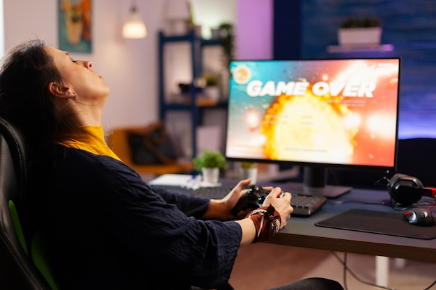 Giocatore donna vincente gioco sparatutto spaziale utilizzando occhiali per realtà virtuale che giocano con il joystick moderno. videogiochi in streaming online per giocatori professionisti con una nuova grafica su un computer potente