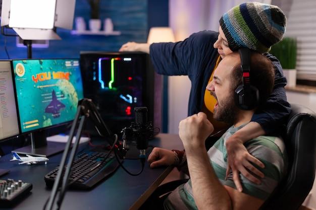 Coppia di giocatori vincendo la competizione di videogiochi online utilizzando attrezzature professionali in home studio. giocatore che gioca ai videogiochi con una nuova grafica su un potente computer da gioco con rgb
