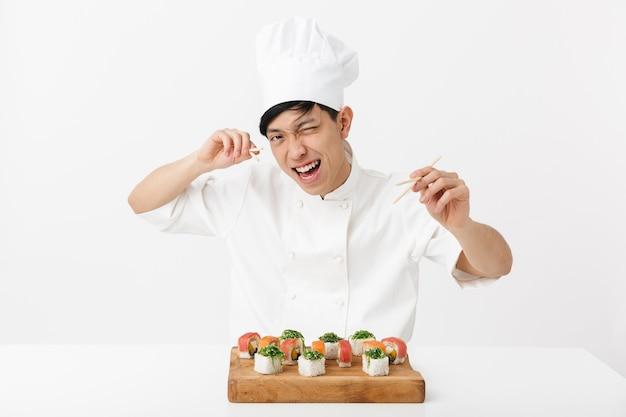 Giocoso capo asiatico in uniforme bianca cuoco mangiare sushi set con le bacchette isolate sul muro bianco
