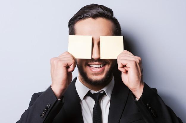 Affari giocosi. ritratto di un giovane sorridente in abiti da cerimonia che si copre gli occhi con le note adesive mentre si trova su uno sfondo grigio