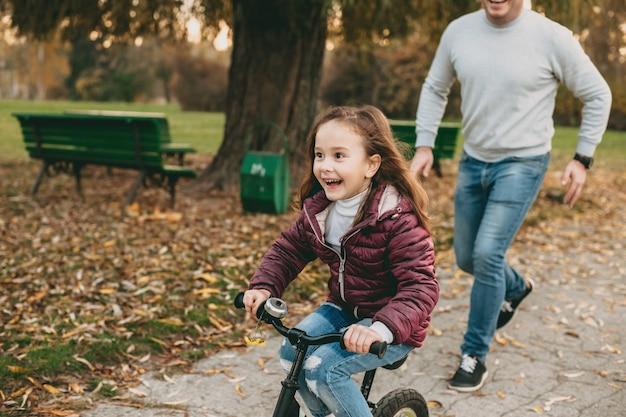 Giocoso padre caucasico che cammina con sua figlia nel parco mentre lei sta andando in bicicletta felicemente