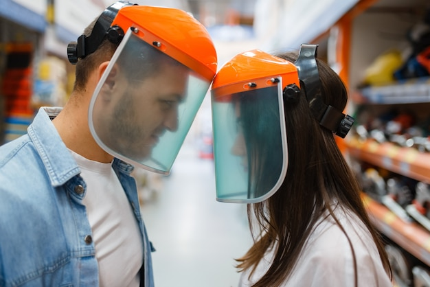 Coppie allegre che scelgono l'attrezzatura nel negozio di ferramenta. i clienti maschi e femmine guardano le merci nel negozio di bricolage