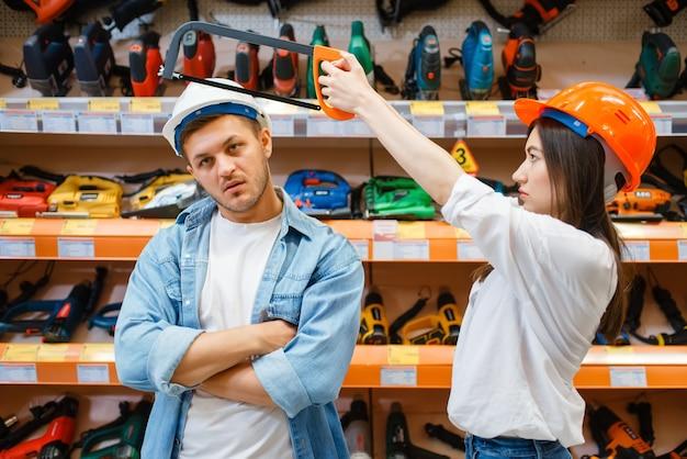 Coppia giocosa scelta di strumenti nel negozio di ferramenta.