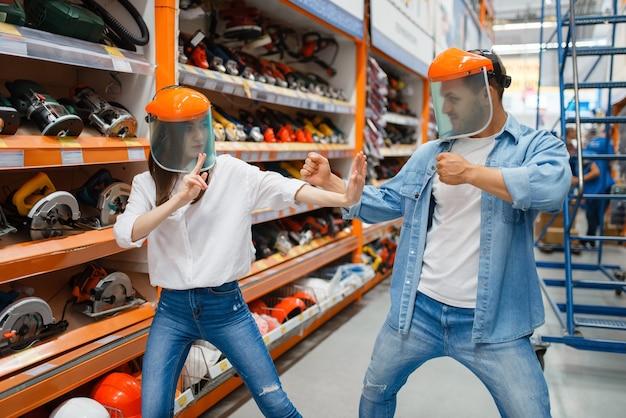 Una coppia giocosa litiga nel negozio di ferramenta come un bambino.