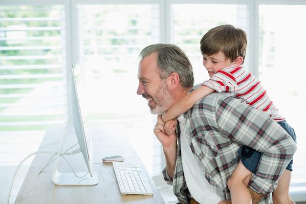 Giocoso padre e figlio che lavorano al computer a casa