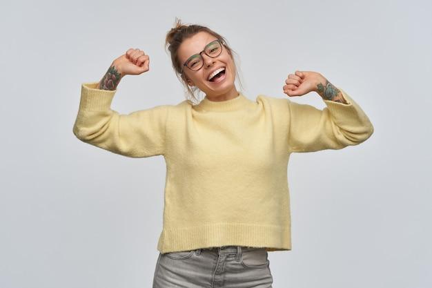 Ragazza allegra con i capelli biondi raccolti in chignon e tatuaggi. indossare occhiali e maglione giallo. alzando le braccia, inclina la testa e sorride. guardando la telecamera, isolata sul muro bianco