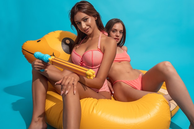 Ragazza allegra con un amico in costume da bagno seduto su un'anatra gonfiabile sulla parete blu