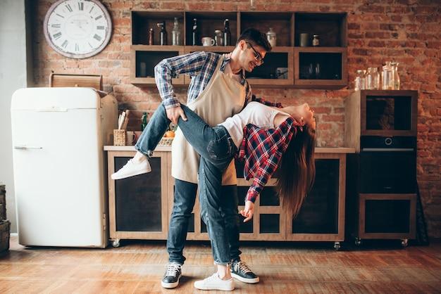 Giocoso amore coppia posa in cucina. l'uomo in grembiule e la giovane donna stanno ballando, cucina divertente